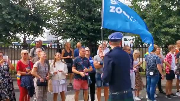 man in uniform and kilt waving a blue flag with the text gewoon zoen, translated just kiss, gay rights activism, LGBT pride parade antwerp, 10 august, 2019, Antwerpen, Belgium