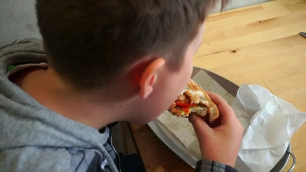 A teenager in a cafe eating a hamburger. He is hungry, slowmotion
