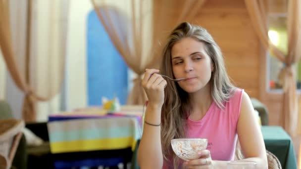Mladá žena v kavárně jíst zmrzlinu. Úsměv