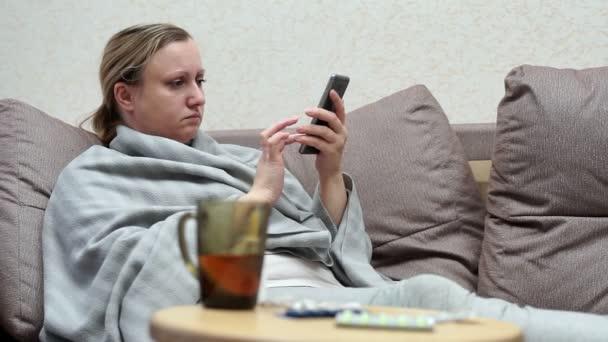 eine Frau hat eine Erkältung zu Hause. mit dem Telefon auf der Couch liegend, mit einer Decke bedeckt. Drogen und Pillen in der Nähe