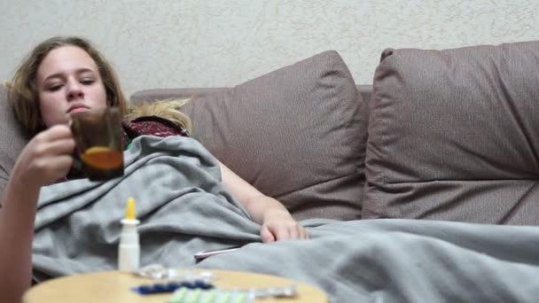 Teenie-Mädchen trinkt Medizin-Tee warm. Liegen auf der Couch mit dem Smartphone