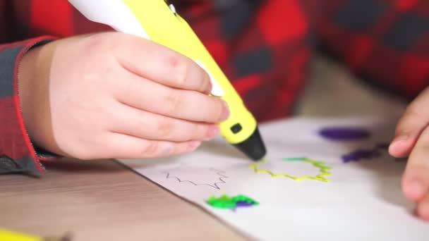 Chlapec dospívající nakreslí plastový obrázek žlutý list. On používá 3d pero