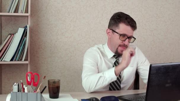 Férfi irodavezető a szakáll és a szemüveg mögött egy laptop dolgozik