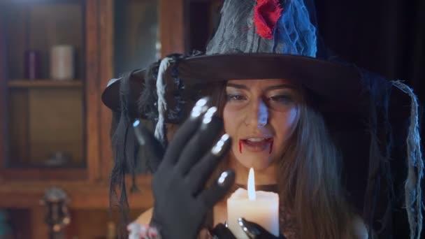 Halloween čarodějnice v klobouku drží svíčku ve svých rukou