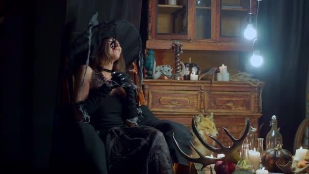 strega oscilla sulla sedia e si presenta con piani malvagi strofinando le mani