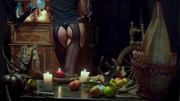 Hexe Halloween sexy Arsch steht. Äpfel und Kerzen auf dem Tisch