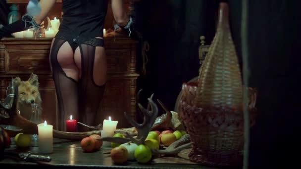 Hexe Halloween sexy Arsch steht. Auf dem Tisch liegen Äpfel, in der Nähe von einem Toten Fuchs
