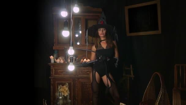 Sexy Halloween-Hexe in einen Hut und Strümpfe mit einer Peitsche. Merkwürdigerweise sieht