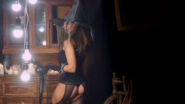 Sexy Halloween-Hexe in einen Hut und Strümpfe mit einer Peitsche. Lächelt spielerisch