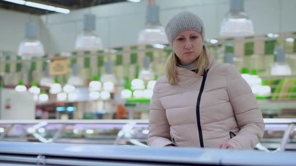 Žena v zimní oblečení chodí kolem supermarketu. Vybírá produkty v lednici v úložišti