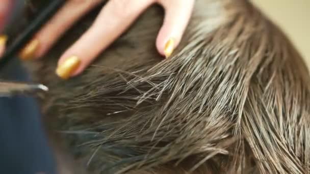 Detailní záběr rukou kadeřníka, který zastřihne vlasy chlapce v kadeřnický salon