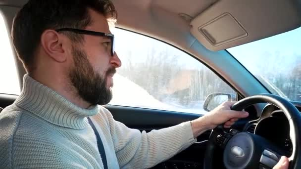 A man drives a car in winter on the highway between cities. Close up profile shot