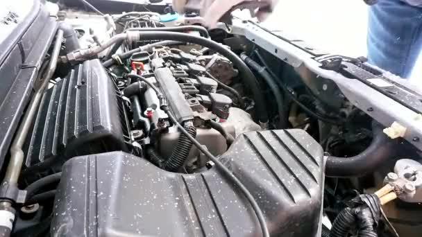 Az autó nem indul, a hideg odakint. ember próbál javítani, és a hideg tél, hogy a régi autó. esik a hó és a hideg az utcán