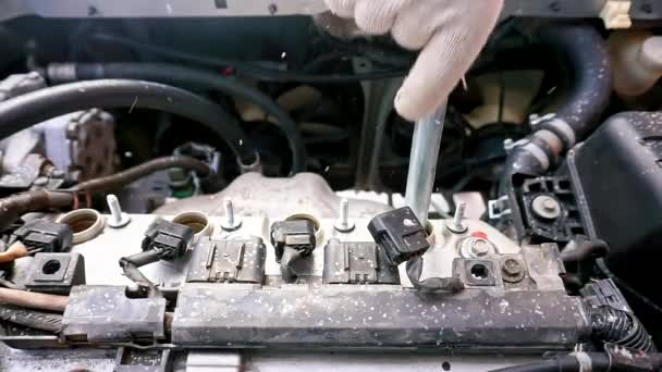 The car will not start, its cold outside. A man unscrews a car engine spark plug.