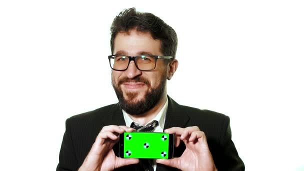 A fogalmi makett. Szakállas üzletember egy smartphone-val egy zöld képernyő névjegykártyaként gazdaság szemüveg