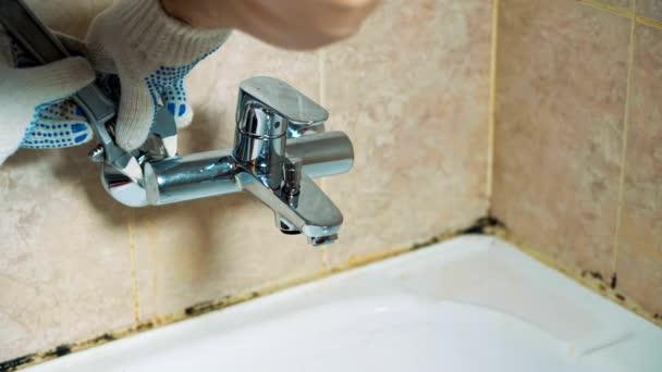 Detail rukavici rukou instalatér nainstaluje kohoutek v koupelně.