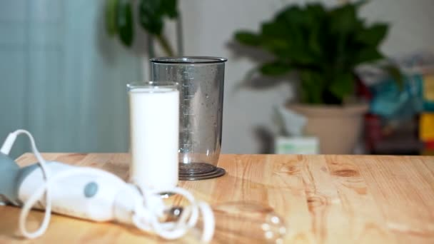 The concept of healthy eating. On the table blender and milk in a glass.