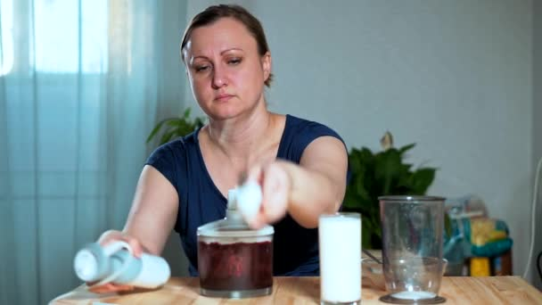 The concept of healthy eating. A woman prepares a blender.