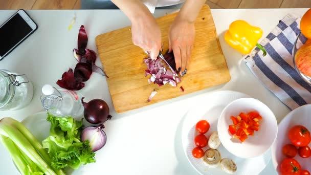 Draufsicht einer jungen Frau aus fein geschnittenen roten Zwiebeln.