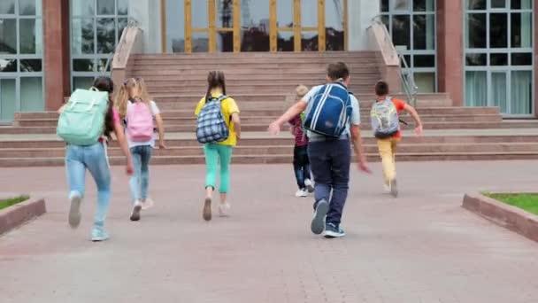 általános iskolások hátizsákkal rohannak az iskolaépületbe