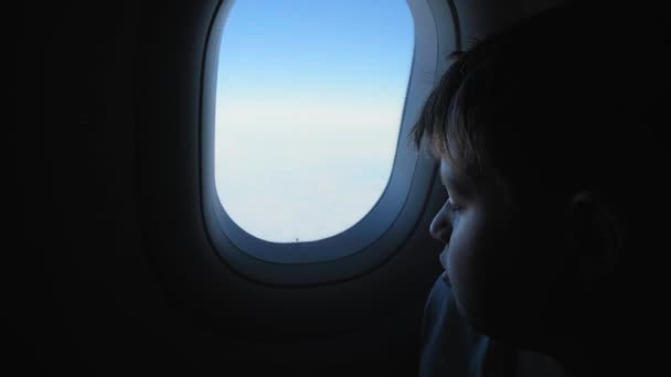 delighted boy admires landscapes outside airplane window