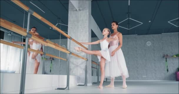 Žena pomáhá holčičce cvičit kladení nohou na tyč