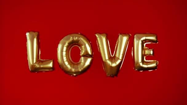 Slovo Love je ve velkých vzdušných zlatých písmenech na červeném pozadí. Nafuatelné koule ve tvaru slova láska. Prohlášení lásky. Objemové dopisy. Blahopřejeme k Valentýnovi, svatbě.