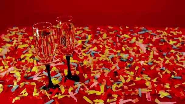 Ein paar Gläser Champagner vor der festlich roten Kulisse, auf dem Tisch ein buntes Konfetti. Glückwunsch Sieg, Hochzeit, Geburtstag, Jubiläum, zum Valentinstag.