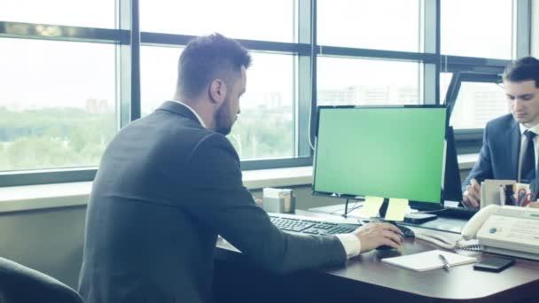 Zaměstnanci společnosti pracují v prostorné světlé kanceláře za počítačové monitory. Úřednice za monitor s zeleným plátnem. Dva mladí podnikatelé v oblecích v práci. Velké panoramatické okno.
