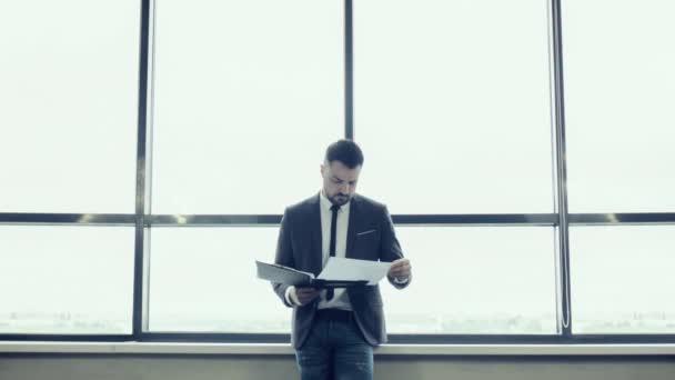 Podnikatel, stojící proti okna kanceláře a čtení dokumentů. Podnikatel, stojící na velké okno vysokého úřadu s panoramatickým výhled. Symetrická kompozice.