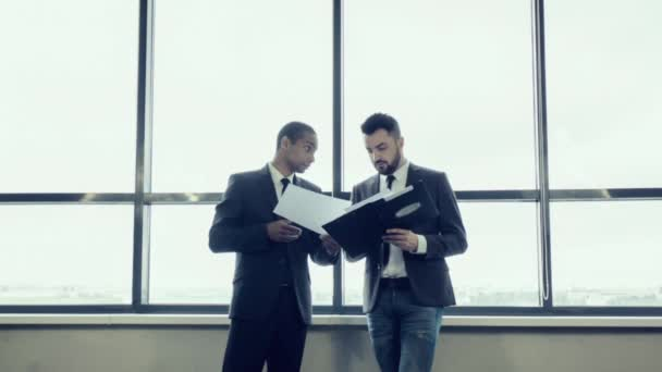 Two businessmen, afro American and Caucasian nationality, in jackets stand near a large panoramic window and discuss the project, review the papers with graphs. International meeting of businessmen.