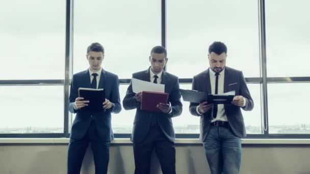 Mladý tým obchodníků v bundy stojí poblíž velké panoramatické okno, kontrola dokumentů s grafy. Mezinárodní tým spolu s africký americký podnikatel. Vyměnit bez upozornění dokumentech.