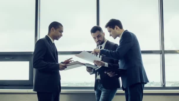 Young team of businessmen in jackets stand near large panoramic window and discuss the project, reviewing papers with graphs. International team along with an African American businessman.