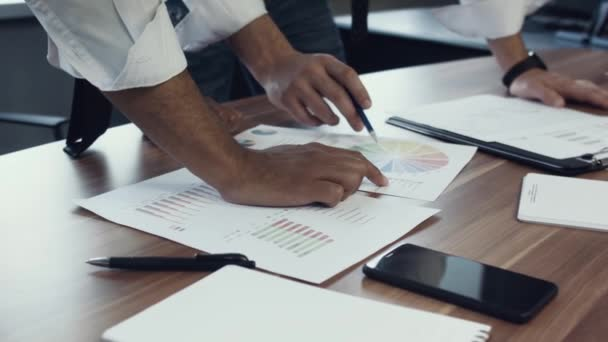 Close-up of hands of businessmen, African and Caucasian nationality at the table and discuss the project, papers with graphs. Work of a business team. Brainstorm.