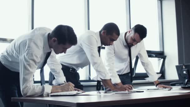 Mladý tým tří podnikatelů, dvě bílé a jeden Africký národní, stend v košile u stolu a diskutovat o projektu, dokumentů s grafy. Práce obchodního týmu. Brainstorm. Panoramatická okna v úřadu
