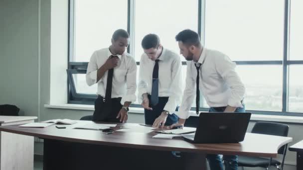 Tým tří podnikatelů, dvě bílé a jeden Africký národní, stend v košile u stolu a bouřlivé diskutovat o projektu, dokumentů s grafy. Práce obchodního týmu. Brainstorm. Panoramatická okna v úřadu