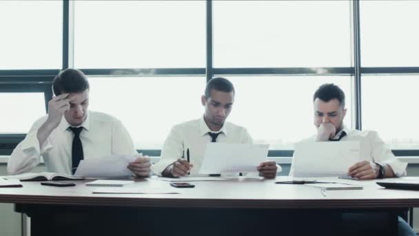 Team of three businessmen in shirts, two caucasian and one african national, sit silently at table. They look and analyze project, papers with charts. Work business team. Panoramic windows in office.