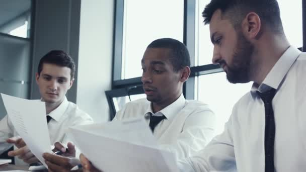 Young team of three businessmen, two caucasian and one african national, sit in shirts at table and discuss project, papers with charts. Work of business team. Brainstorm. Panoramic windows in office.