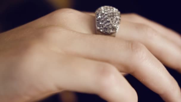 Diamond ring on womans hand. Large white gold ring with numerous diamonds on the finger of the girl close-up.