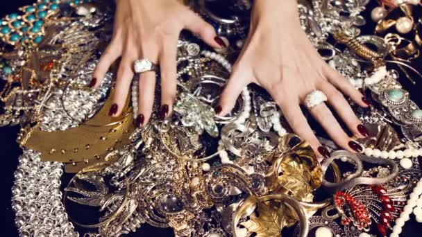 Female hands with a large ring of gold with precious stones touch a bunch of gold and silver jewelry on a black background. Luxurious life. Incredible wealth. Hidden treasures.