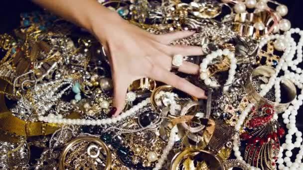 Ženská ruka s velký prsten ze zlata s drahými kameny dotkne hromadu zlatých a stříbrných šperků na černém pozadí. Luxusní život. Neuvěřitelné bohatství. Skryté poklady.