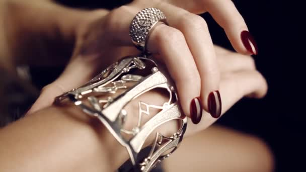 Detail z krásných ženských rukou s červenými nehty s velký náramek a diamantový prsten. Zlaté šperky pro ženy. Luxusní život. Reklamní šperky. Ve studiu na černém pozadí