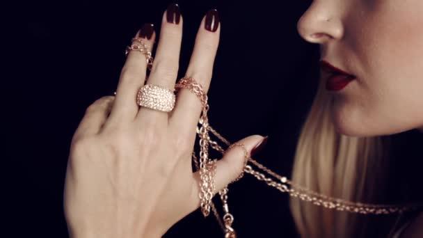 Detail dívčí ruky červenou nehty drží zlatý řetízek. Šperky pro ženy. Ve studiu na černém pozadí. Velký zlatý prsten s diamanty na prst.