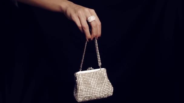Ženská ruka drží vintage elegance kabelky zdobené diamantem izolované na černém pozadí. Kabelky vyrobené z diamantů. Ženské šumivé glamour Luxusní stříbrné diamantové kabelka kabelka