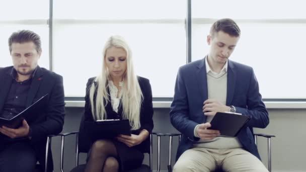 Podnikatelé, čekání na pohovor. Tři kandidáti soutěžit o jednu pozici s Projděte si také anglickou v ruce. Skupina, stresující vysokoškoláků, čekání na zkoušku testu.