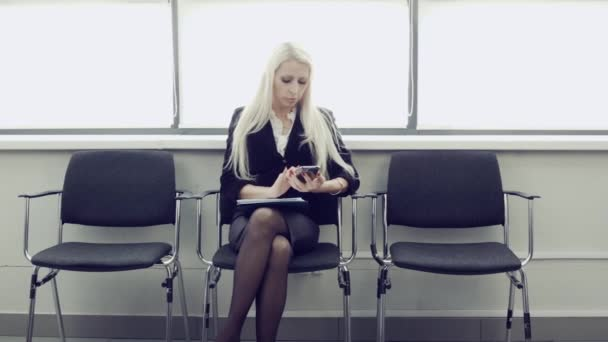 Woman sittin on chair waiting for job interview. Business woman in a strict suit is waiting for an interview and uses a smartphone.
