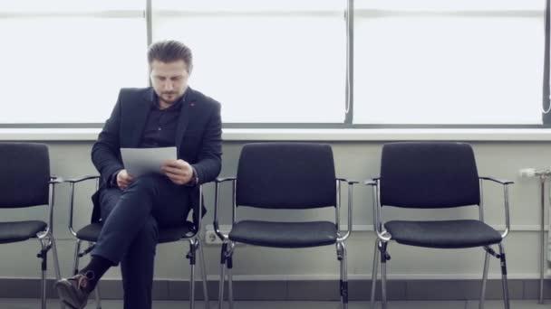 Připraveni na pohovor přemýšlivého člověka v oblasti formální oblečení drží papír sedí na židli v kanceláři hall. Podnikatel, sedí na židli při čekání na letišti pokoji a prohlížení dokumentů.
