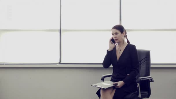 Adult businesswoman is sitting in leather chair in spacious bright office and talking on smartphone. Female entrepreneurship.  Successful business lady. Conceptual advertising for business.