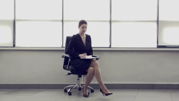 Adult businesswoman sits in leather chair in spacious bright office and signs documents and contracts. Female entrepreneurship. Conceptual advertising for business. Successful business lady.