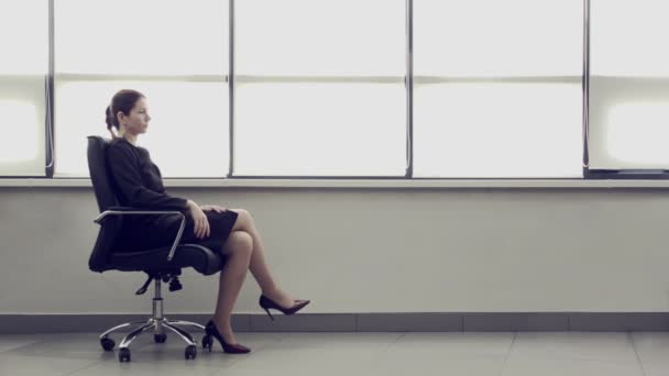 Adult business woman sits in leather chair in a spacious bright office. Female entrepreneurship. Conceptual advertising for business. Successful business lady. Space for logung, text.